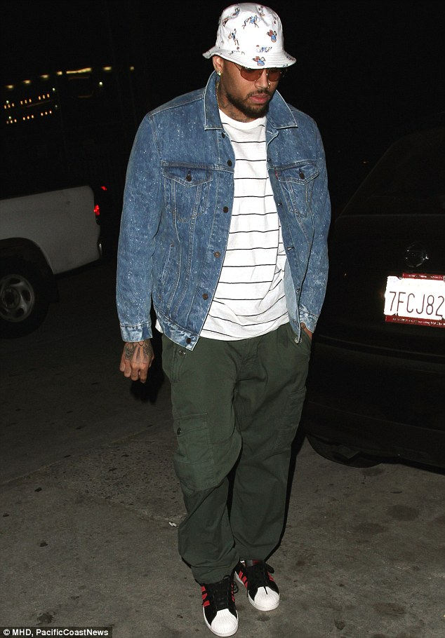 Looking down: a casually dressed Chris Brown leaves Katsuya in Hollywood before heading to a nearby recording studio