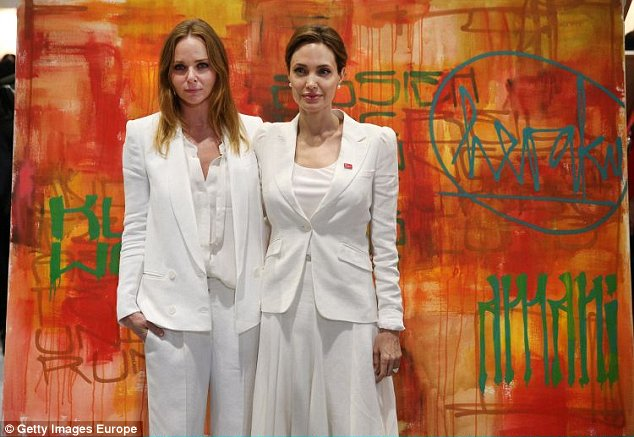 LONDON, ENGLAND - JUNE 10:  UN Special Envoy and actress Angelina Jolie (R) stands with designer Stella McCartney infront of an unfinished 'Herakut' painting at the Global Summit To End Sexual Violence In Conflict on June 10, 2014 in London, England. The four-day conference on sexual violence in war is hosted by Foreign Secretary William Hague and UN Special Envoy and actress Angelina Jolie.  (Photo by Peter Macdiarmid/Getty Images)