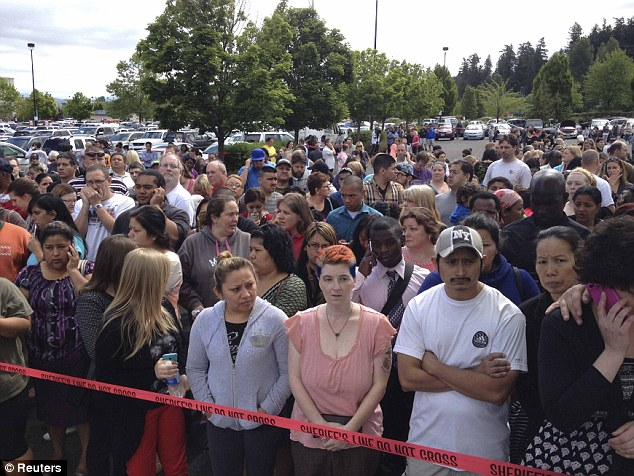 Anxious: Parents wait behind police tape for students from Reynolds High School to arrive by bus in Troutdale, Oregon June 10, 2014