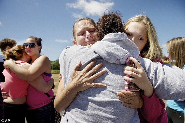 Frightened: Brandi Wilson, (left), and her daughter, Trisha Wilson, 15, (right), embrace Trish Hall, a mother waiting for her student, as students arrived at the Fred Meyer grocery store parking lot