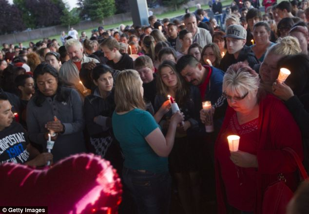 Friends, family and well-wishers hold candles for Emilio Hoffman, the victim of a school shooting