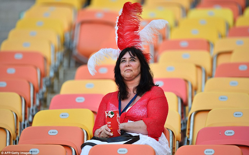 Is there something on my head? An early arrival to the stadium clutches a branded cup as she waits for the kick-off - and there's no prizes for guessing who she supports
