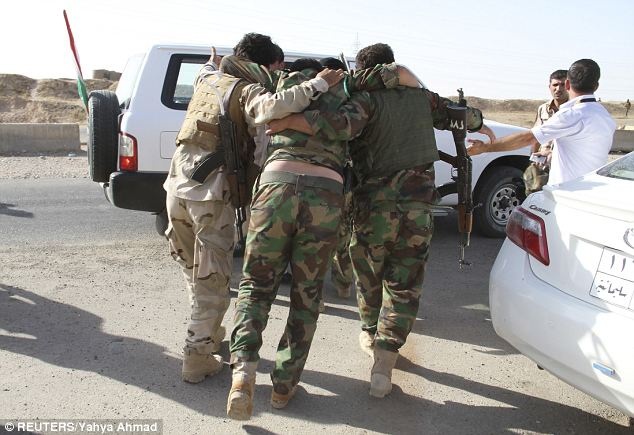 Les membres des forces de sécurité kurdes aider leur collègue qui a été blessé lors d'affrontements avec ISIS