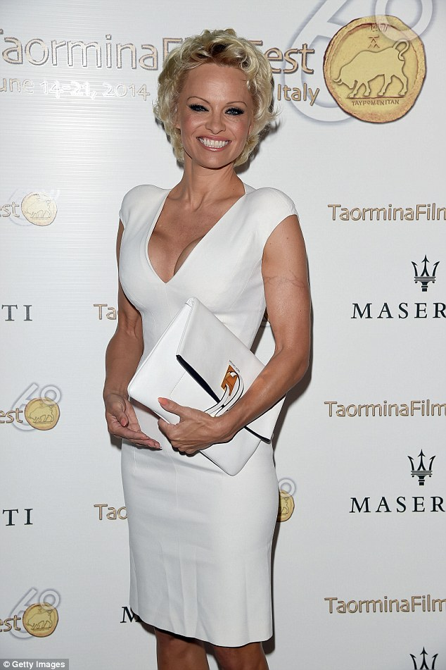 Taking the plunge: Pamela Anderson showed off her full cleavage and toned arms in a figure-hugging white dress while at the Taormina Film Festival in Taormina, Italy on Sunday