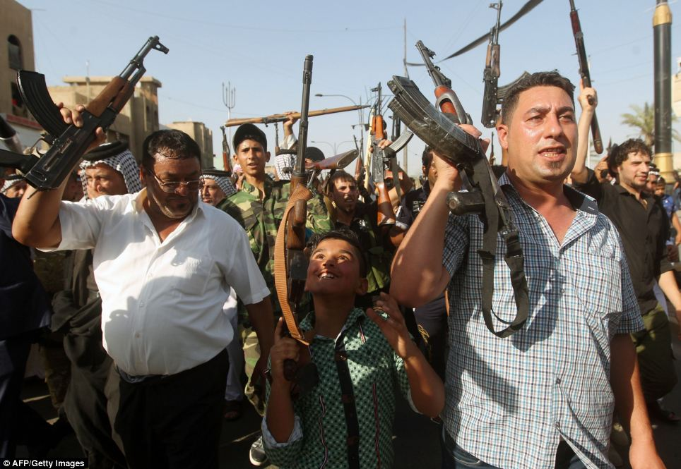 A Iraqi young boy and tribesmen hold up their weapons  in the capital Baghdad today as they prepare for an ISIS attack