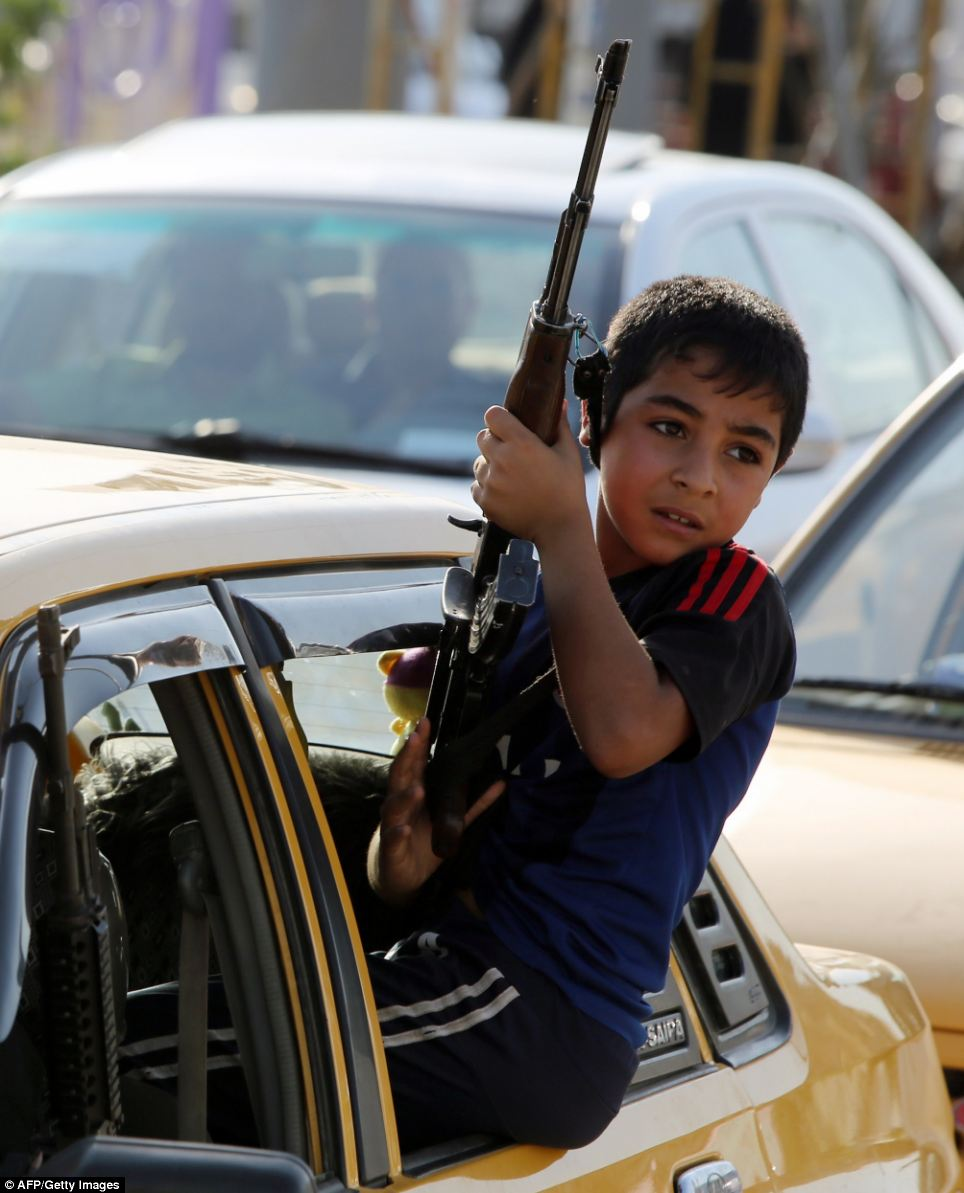 An Iraqi young boy holds a weapon from the window of a car as people gather to show their readiness to join Iraqi security forces in the fight against Jihadist militants