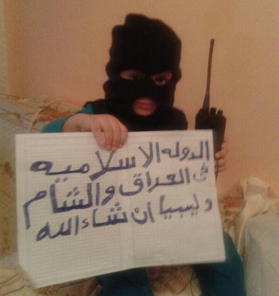 Young jihadi: A child is pictured on an ISIS-supporting Twitter feed wearing a balaclava and holding a sign saying 'God is greatest'