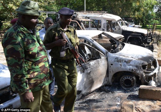 Kenya police observe the remains of burnt-out cars at a police station in Mpeketoni.  Kenya's tourist board in London has attempted to play down the threats in a bid to save the tourism industy