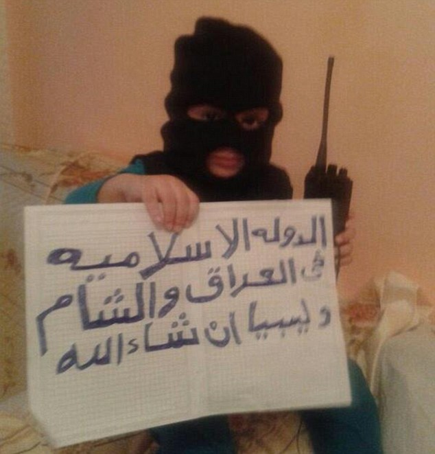 Young jihadi: A child is pictured on of the ISIS-supporting Twitter feeds wearing a balaclava and holding a sign saying 'God is greatest'