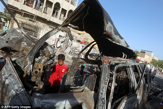 Terror blast: Iraqis inspect the site of a car bomb explosion in the Shi'ite Sadr City district of Baghdad which killed at least 12 people and wounded dozens more this morning
