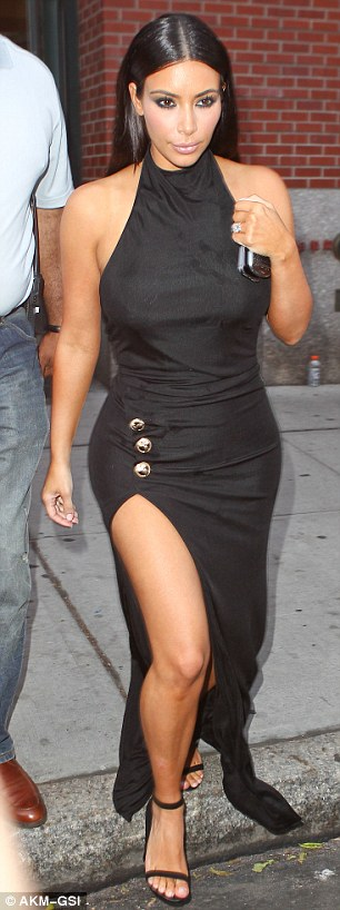 Thigh's the limit: Kim shows off her figure in a black halterneck dress