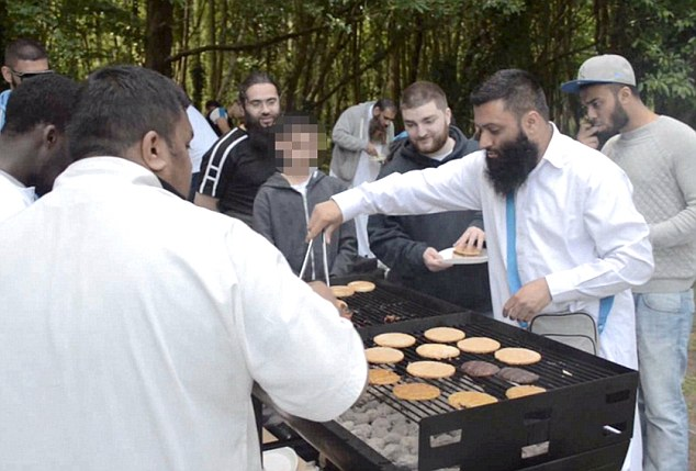 Event: Abu Waleed, who lives in west London, dishes out burgers at a barbecue in Cardiff earlier this month