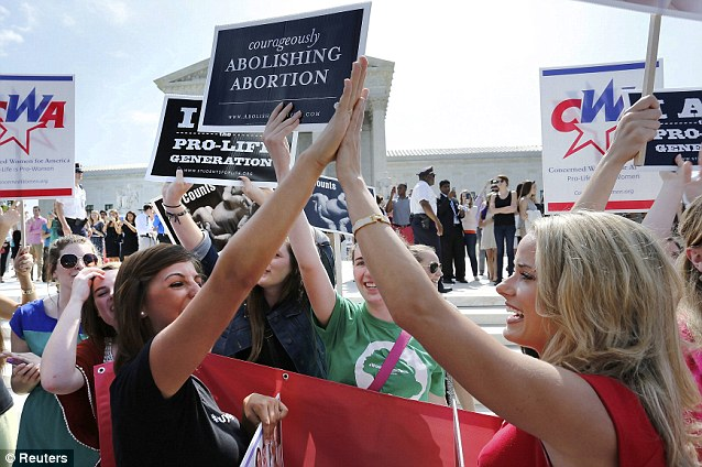 Concerned Women for America communications director, Alison Howard, right, high fives another pro-life demonstrator outside the Supreme Court after learning that Hobby Lobby won its case against the government