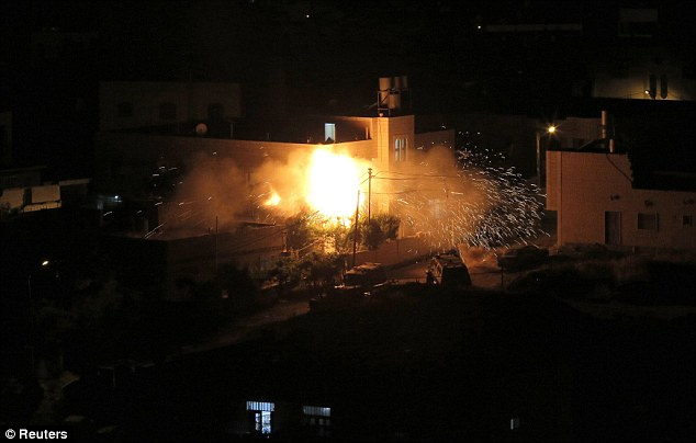 Homes decimated: Flames are seen after a blast on the top floor of the family home of an alleged abductor in the West Bank City of Hebron July 1