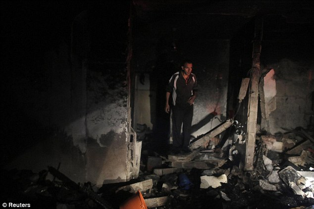 Destruction: Troops set off explosions in the family homes of the alleged abductors, blowing open a doorway in one, an army spokeswoman said, while television footage showed the other on fire after the blast. Neighbous said both houses were empty