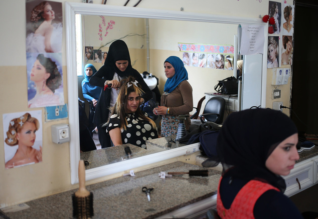 In this photo taken on May 29, 2014, Syrian refugee women attend a hair dressing class where they obtain crucial training to find jobs in a community center ...