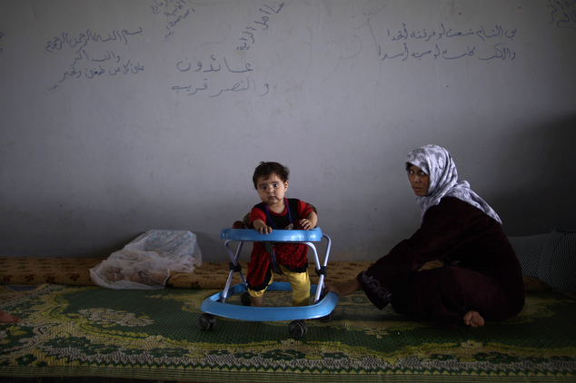 FILE - In this Wednesday, Sept. 12, 2012, file photo, a Syrian woman and her daughter, who fled their home due to fighting between the Syrian army and the re...