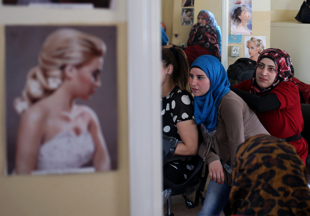 In this picture taken on May 29, 2014, Syrian refugee women reflected by a mirror attend a hair dressing class where they obtain crucial training to find job...