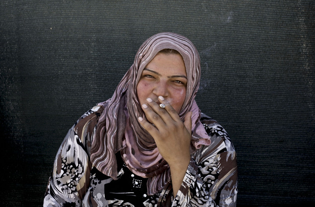 FILE - In this Wednesday, Sept. 11, 2013, file photo, a Syrian refugee woman smokes a cigarette outside of her tent at a temporary refugee camp in the easter...