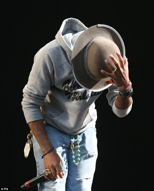 Hats off: Pharrell bows to the audience and makes sure he doesn't lose his beloved headwear