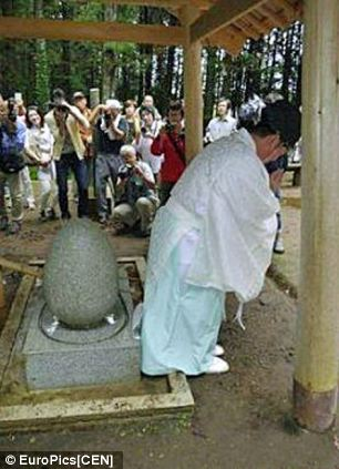 Temple priest Osamu Hayakawa demonstrating the ritual he claims will cure visitors of haemorrhoids