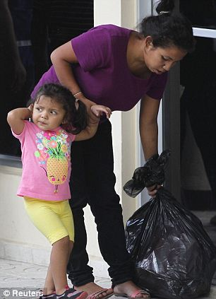 A woman holds her daughter's hand as she grabs a plastic bag with their belongings, after being deported from the U.S. at the international airport in San Pedro Sula, northern Honduras July 14, 2014. The U.S. deported a group of Honduran children on Monday in the first flight since President Barack Obama pledged to speed up the process of sending back illegal immigrant children from Central America. Monday's charter flight from New Mexico to San Pedro Sula, the city with the highest murder rate in the world, deported 17 Honduran adult women, as well as 12 girls and nine boys, aged between 18 months and 15 years, the Honduran government said. REUTERS/Jorge Cabrera (HONDURAS - Tags: POLITICS SOCIETY IMMIGRATION)