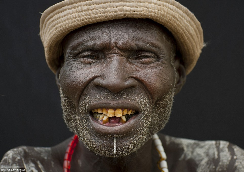 African man smiling into camera with missing teeth