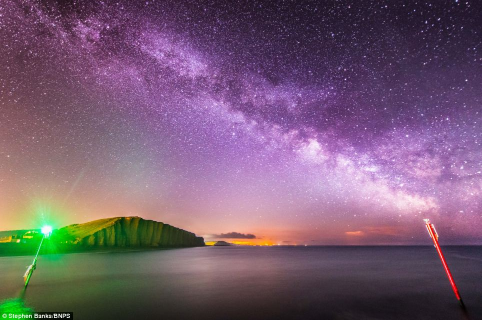 These sensational celestial snaps show the Milky Way in all its glory over a series of stunning countryside landscapes. They were taken by amateur photographer Stephen Banks, 25, who has spent the last two years learning how to capture the night sky. This stunning picture of West Bay captures the headlights from a truck parked at the cliff top which look more like beams from an alien spacecraft