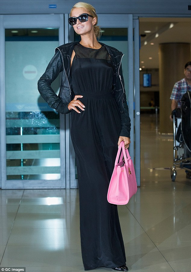 Covering up: Paris Hilton hid her bikini body in a baggy black jumpsuit as she arrived at the Incheon International Airport in South Korea on Wednesday