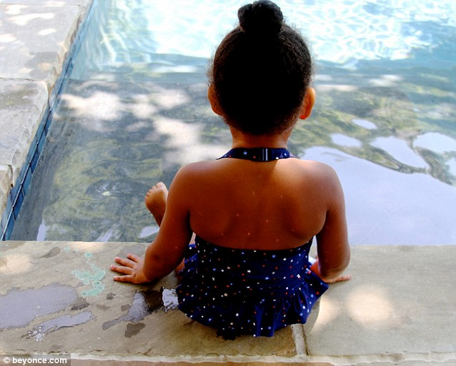 Growing up fast: Two-year-old Blue Ivy sits on the edge of a pool in a spotted swimsuit in this image from Beyonce's website