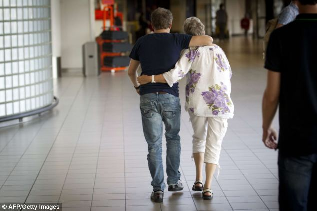 A couple walks towards the information point at Schiphol Airport that has been set up for loved ones of passengers travelling on flight MH17
