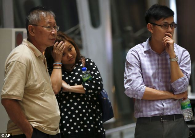 A family anxiously await news of passengers on flight MH17 at Kuala Lumpur International Airport early on Friday morning local time