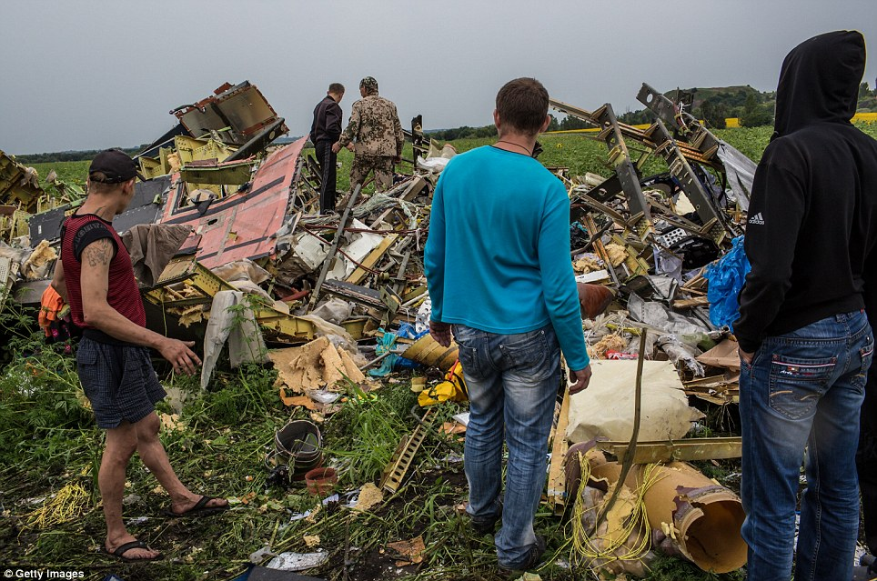 Stunned: Ukrainians inspect the wreckage of MH17 as coal miners, farmers and other volunteers help with the grisly task of clearing up the crash sites after the Malaysia Airlines jet was shot down by a surface-to-air missile over the east of the country