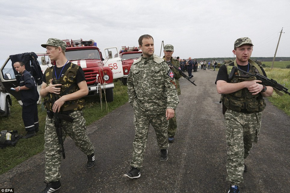Blame game: The pro-Russian self-proclaimed governor of the Donetsk region Paul Gubarev (centre) is surrounded by armed guards as he looks at debris of the Boeing