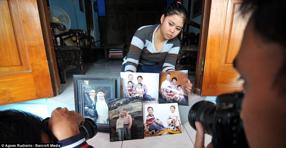 Devastation: A surviving relative shows photographers images of the family, who were on the doomed plane