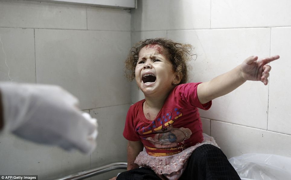 Terrified: A Palestinian child shouts at doctors at al-Shifa hospital. But Israeli public opinion appears to strongly support the offensive after days of unrelenting rocket fire from Gaza and years of southern Israeli residents living under the threat
