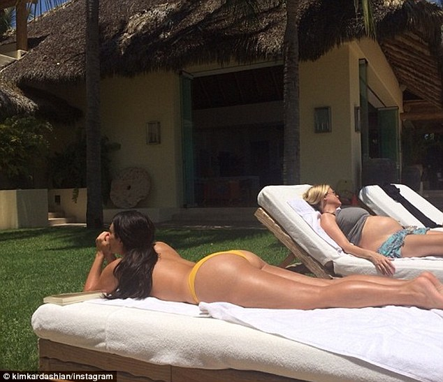 Beach babes: Kim shared this snap of her and Abbey sunbaking with the caption '#OurLovelyLadyLumps'