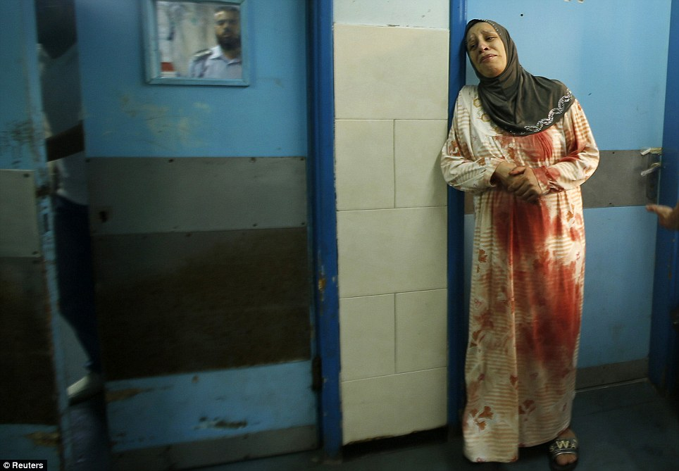 A Palestinian woman wearing clothes stained with the blood of other relatives, who medics said were wounded in Israeli shelling, cries at a hospital in Gaza City