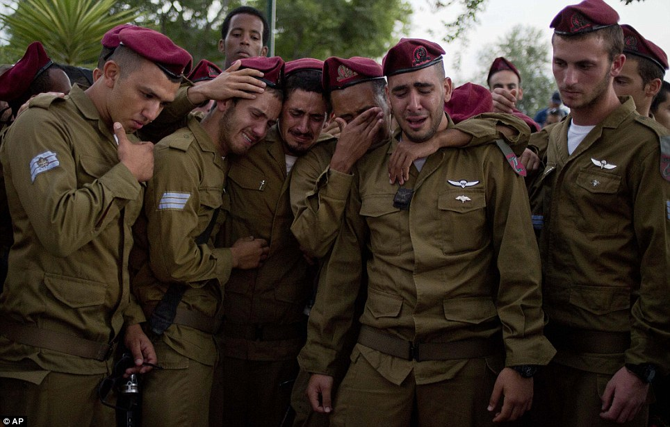 Grief: Israeli soldiers of the Paratroopers Brigade mourn over the grave of Sgt. Bnaya Rubel during his funeral