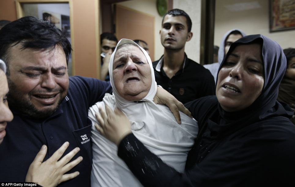 Distraught: The relatives of a patient killed in the Israeli army shelling are pictured clinging on to each other as they weep for their loved one