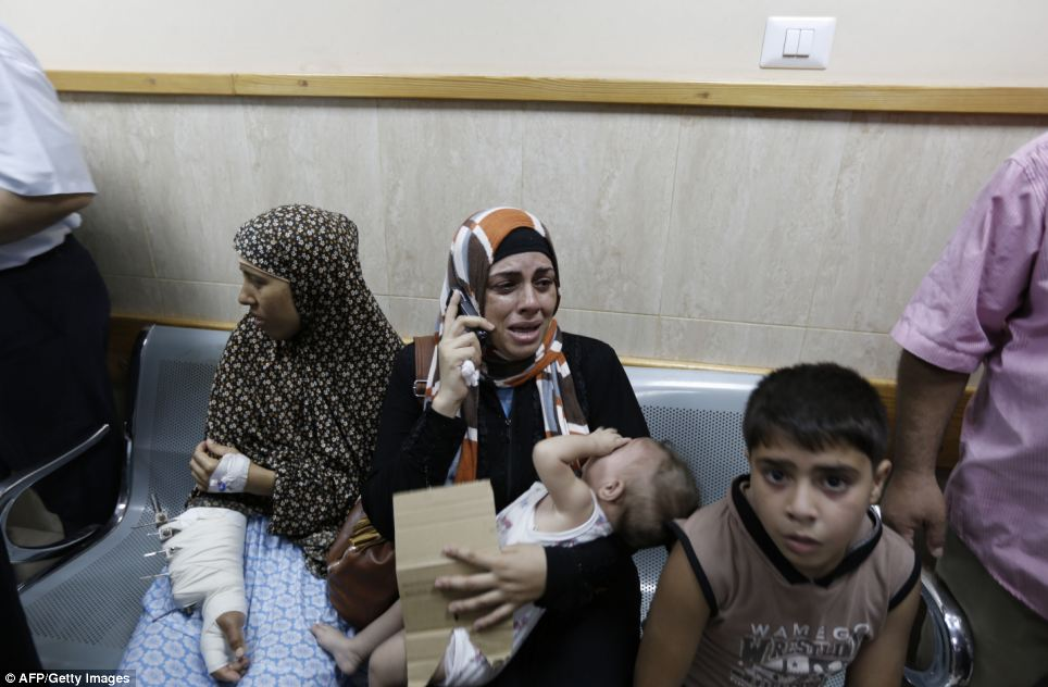 Patients: A woman cries as she speaks on the phone at Al-Aqsa Martyrs hospital in Deir al-Balah, central Gaza, which was hit by Israeli tank shells today