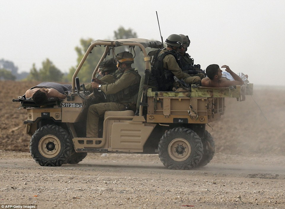 Israeli soldiers evacuate their wounded comrades at an army deployment area near Israel's border with the Gaza Strip