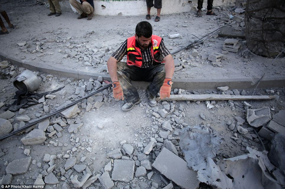 A Palestinian firefighter rests while searching for the dead and injured during the temporary ceasefire