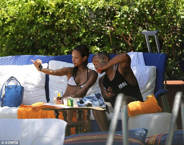 Say cheese: As her friend enjoyed a cocktail, Karrueche was preoccupied with taking selfies