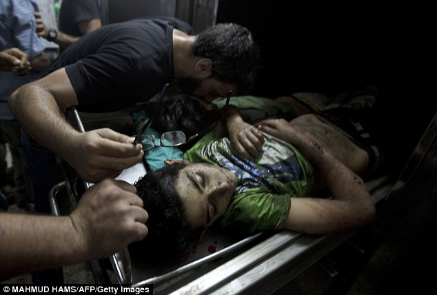 A man kisses the body of a dead child at the mortuary of the Shifa Hospital in Gaza City