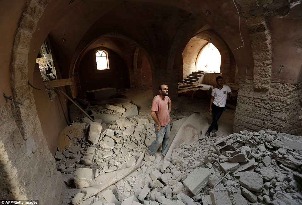 Rubble: Palestinian men inspect the damage at the historic al-Omeri mosque in Jabalia in the northern Gaza Strip. The death toll stands at more than 1,650 as Israel and Hamas trade accusations over the timing of yesterday's raid, which Israel said led to the kidnapping of23-year-old Israeli Lieutenant Hadar Goldin. He remained missing