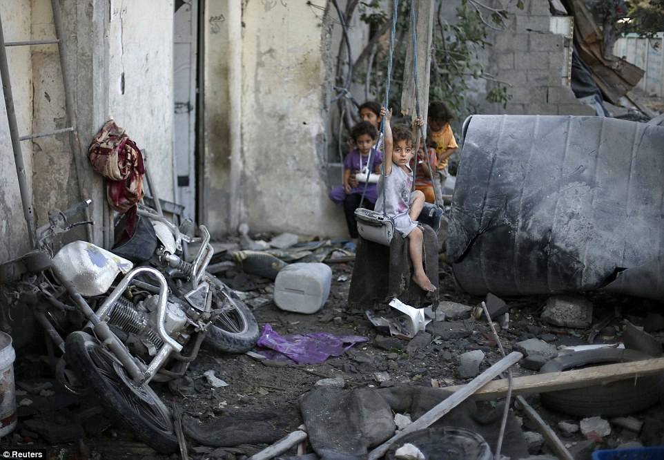 Playtime no more: A Palestinian girl sits on a swing outside her family's home in Gaza City, which witnesses said was damaged today in an Israeli air strike