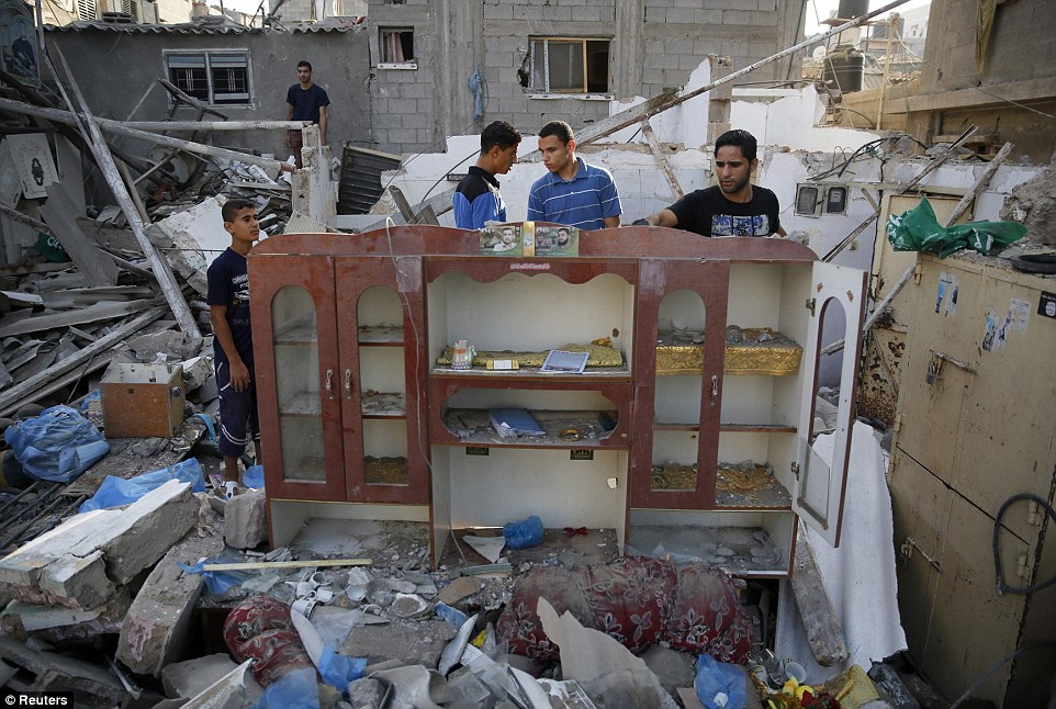 Salvage: Young Palestinian men rescue belongings from a house in the Shati refugee camp in Gaza City as both sides trade blame over the latest wave of bloodshed