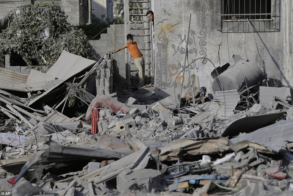 Looking out of the front door: A man and a boy inspect the damage after overnight air strikes in Gaza City. The conflict has claimed more than 1,650 Palestinian lives
