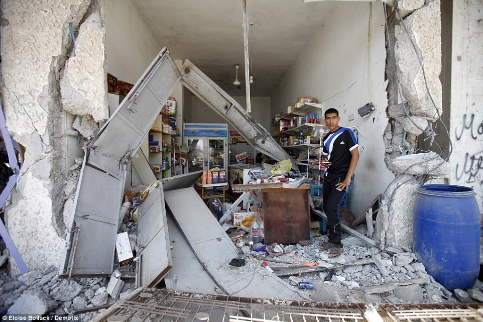 Remnants: A Palestinian man stands today in what was once his store, destroyed during the bombardment of Khuzaa in south eastern Gaza Strip